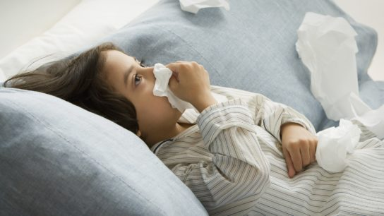 sick child blowing his nose
