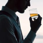 man drinking glass of alcohol